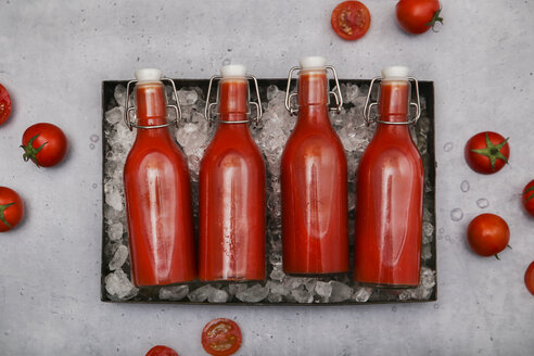 Row of four ice-cooled swing top bottles with homemade tomato juice - RTBF01258