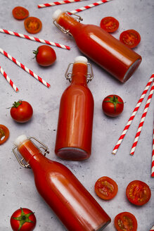 Homemade tomato juice in swing top bottles, straws and tomatoes on grey ground - RTBF01267