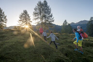 Family hiking in alpine meadow at sunset - HHF05556