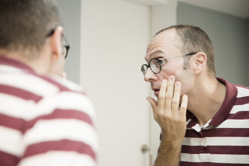 Over shoulder view of mature man looking at his face in bathroom mirror - CUF02769