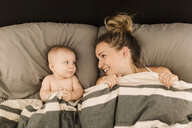 Woman lying in bed under duvet with baby daughter, overhead view - CUF02784