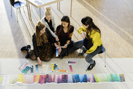 Colleagues sitting on floor working with colour swatches - CUF02811