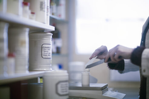 Male pharmacist weighing medical drug on pharmacy scales, cropped - CUF02865