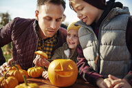 Man with son and daughter looking at carved halloween pumpkin at pumpkin patch - CUF02913