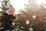 Girl looking at baubles on forest christmas tree - CUF02925
