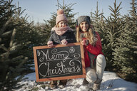 Girl and mother in christmas tree forest with merry christmas sign, portrait - CUF02928