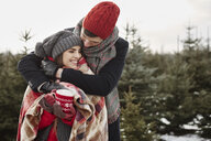 Romantic young couple in christmas tree forest wrapped in blanket - CUF02931