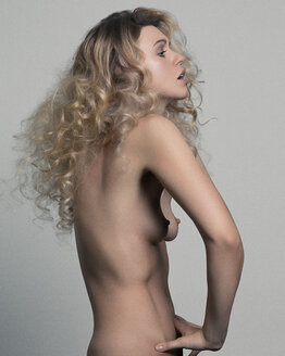 Nude studio portrait of young woman with hands on stomach, side view - CUF02946