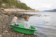 Boys in green boat at fjord water's edge, Aure, More og Romsdal, Norway - CUF03015