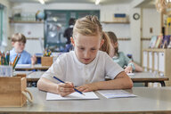 Schoolgirl writing in classroom lesson in primary school - CUF03060