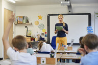 Schoolboy with hand raised in classroom lesson at primary school - CUF03066