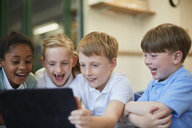 Schoolboys and girls laughing at digital tablet in classroom at primary school - CUF03078