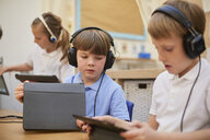 Schoolboys and girl listening to headphones in class at primary school - CUF03084