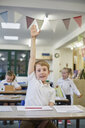 Schoolboy with hand up in classroom at primary school - CUF03108