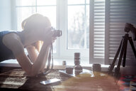 Mid adult woman, beside window, looking through camera, camera lenses on table in front of her - CUF03111
