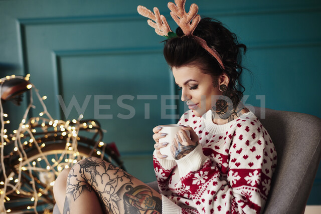 Young woman sitting at home, wearing christmas jumper and antlers, drinking hot drink - CUF03120
