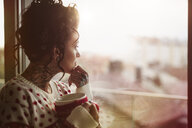 Young woman looking out of window, holding hot drink, thoughtful expression - CUF03123