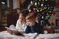 Young girl and boy relaxing beside Christmas tree, reading book - CUF03132