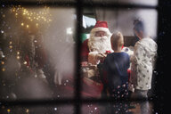 Young girl and boy receiving gifts from Santa, viewed through window - CUF03138