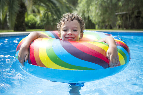 Boy with inflatable ring in outdoor swimming pool, portrait - CUF03177