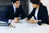 Businessman and woman in meeting, businesswoman looking at smartphone - CUF03234