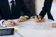 Businessman and woman in meeting, signing documents, mid section - CUF03237