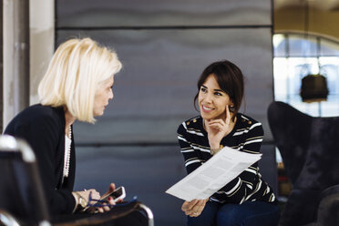 Two businesswomen in meeting, looking at document - CUF03240