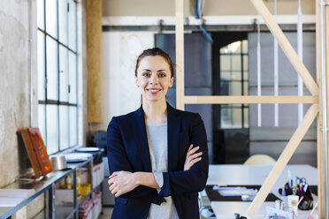 Portrait of businesswoman in office, arms folded, smiling - CUF03246