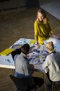 Male and female designers discussing colour swatches on design studio table - CUF03264