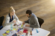 Male and female designer discussing colour swatches on design studio table - CUF03267