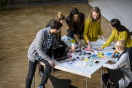 Team of male and female designers discussing colour swatches on design studio table - CUF03270