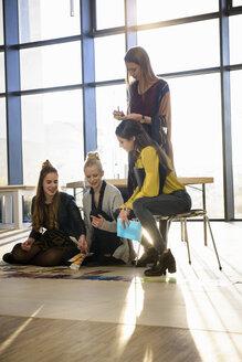 Team of female designers looking at colour swatches on design studio floor - CUF03276