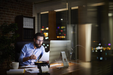 Young businessman reading paperwork and eating takeaway at office desk at night - CUF03300