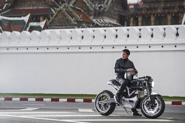 Man with electric motorbike by royal palace, Bangkok, Thailand - CUF03321