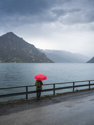 Italy, Lombardy, back view of senior woman with backpack and red umbrella looking at Lake Idro - LAF02028