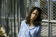 Portrait of beautiful young woman leaning against a fence - JRFF01629
