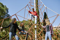 Happy friends at a climbing frame on a playground - JRFF01638