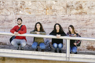 Portrait of four happy friends crouching at stone wall - JRFF01641