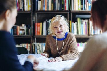Three businesswomen, sitting around table, looking through documents - CUF03471
