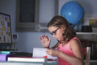 Young girl sitting at desk, doing homework, looking through book - CUF03513