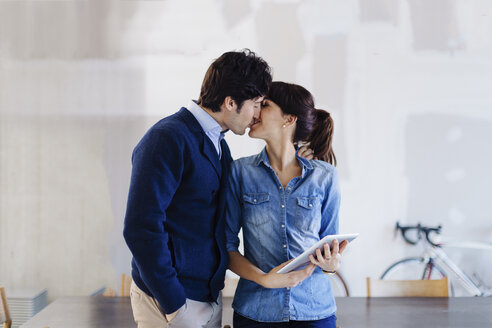 Businessman and woman in office, kissing, woman holding digital tablet - CUF03525