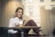 Mid adult woman in cafe window seat using digital tablet - CUF03627