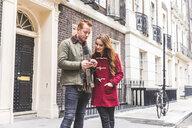 Couple chatting on street, London, UK - CUF03690