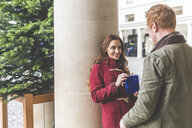 Man and woman chatting against column, Covent Garden, London, UK - CUF03696