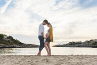 Pregnant woman and man standing face to face on beach, holding hands - CUF03705