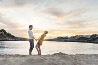Pregnant woman and man face to face on beach, holding hands, laughing - CUF03708