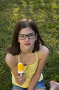 Portrait of girl wearing glasses sitting on a meadow eating ice lolly - LVF06961