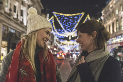Two female friends standing in illuminated street at night - CUF03805