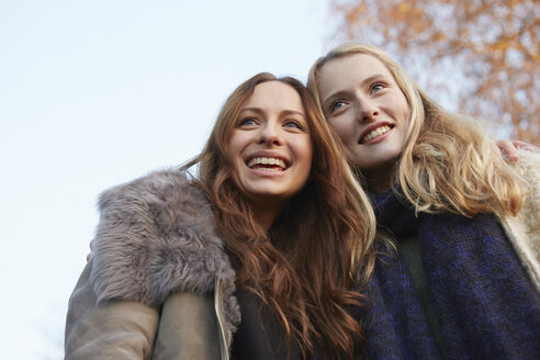 Two female friends, walking outdoors, smiling - CUF03934
