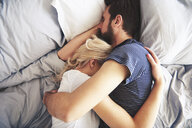 Couple lying in bed together, sleeping, arms around each other - CUF03946